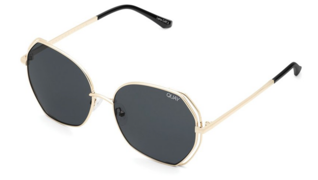 UNIKONCEPT: Lifestyle boutique; Image shows a pair of rounded framed Quay sunglasses. The big love sunglasses in gold/ smoke feature a smoke coloured lens with a gold geometric frame, It has a double layer of metal wiring around the side of the frame.