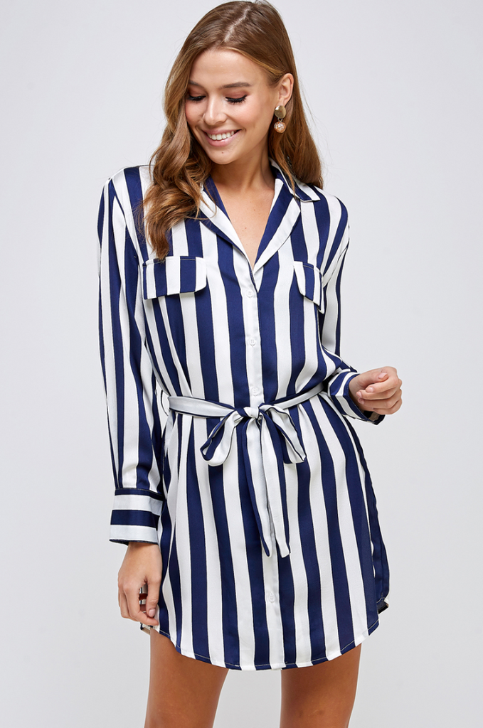 UNIKONCEPT: Liefstyle boutique; image shows a long sleeve tunic styled shirt dress by Ark&Co. The Hey sailor shirt dress features a collared neckline with vertical navy and white stripes throughout. It is long sleeve with two small pockets on the chest, it also features vertical buttons down the middle of the shirt dress and a small fabric belt to sinch the waist.