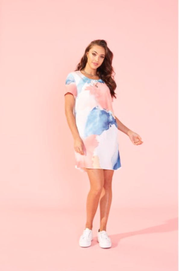 UNIKONCEPT: Lifestyle boutique; image shows a tee shirt style dress by mink pink. The bene tee dress features a rounded neck line, tee shirt sleeves, is a mini style and has a watercolour print throughout with bright blue, pink, yellow and orange colouring.