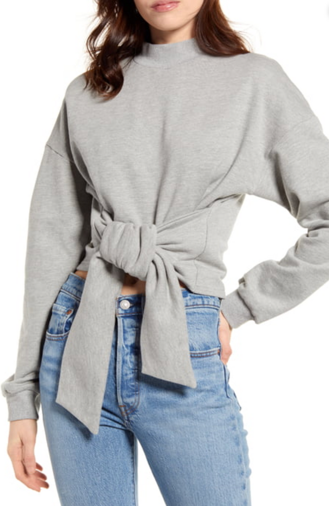 UNIKONCEPT: Lifestyle boutique; image shows a long sleeve grey sweater by Minkpink. The tie front top by mink pink feature a mock neckline, two large pieces of fabric that tie together at the waistline and puffy sleeves.