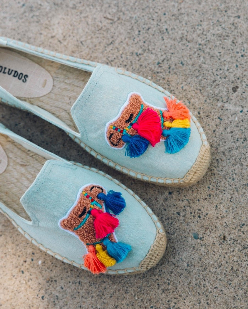 UNIKONCEPT Lifestyle boutique: Pictured here is a flat lay of baby blue espadrille soludos shoes. The tassel camel smoking slipper comes with a 1 inch straw platform throughout the sole. On the instep the shoe features a camel embroidered with blue, yellow and red tassels.