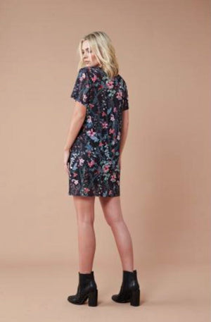 Model is wearing black, sheer t-shirt, loose dress. The dress features a black spandex slip dress underneath and pink and green small floral details on the outer sheer dress.