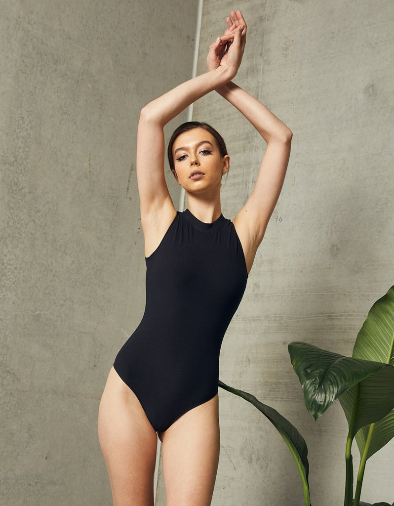 UNIKONCEPT LIFESTYLE BOUTIQUE: This model is wearing the Melbourne Bodysuit by Dream Bandits in the colour black. The bodysuit has a high mock neckline and is sleeveless with a high cut brief, including 3 crotch clippers for various sizing and comfortability.