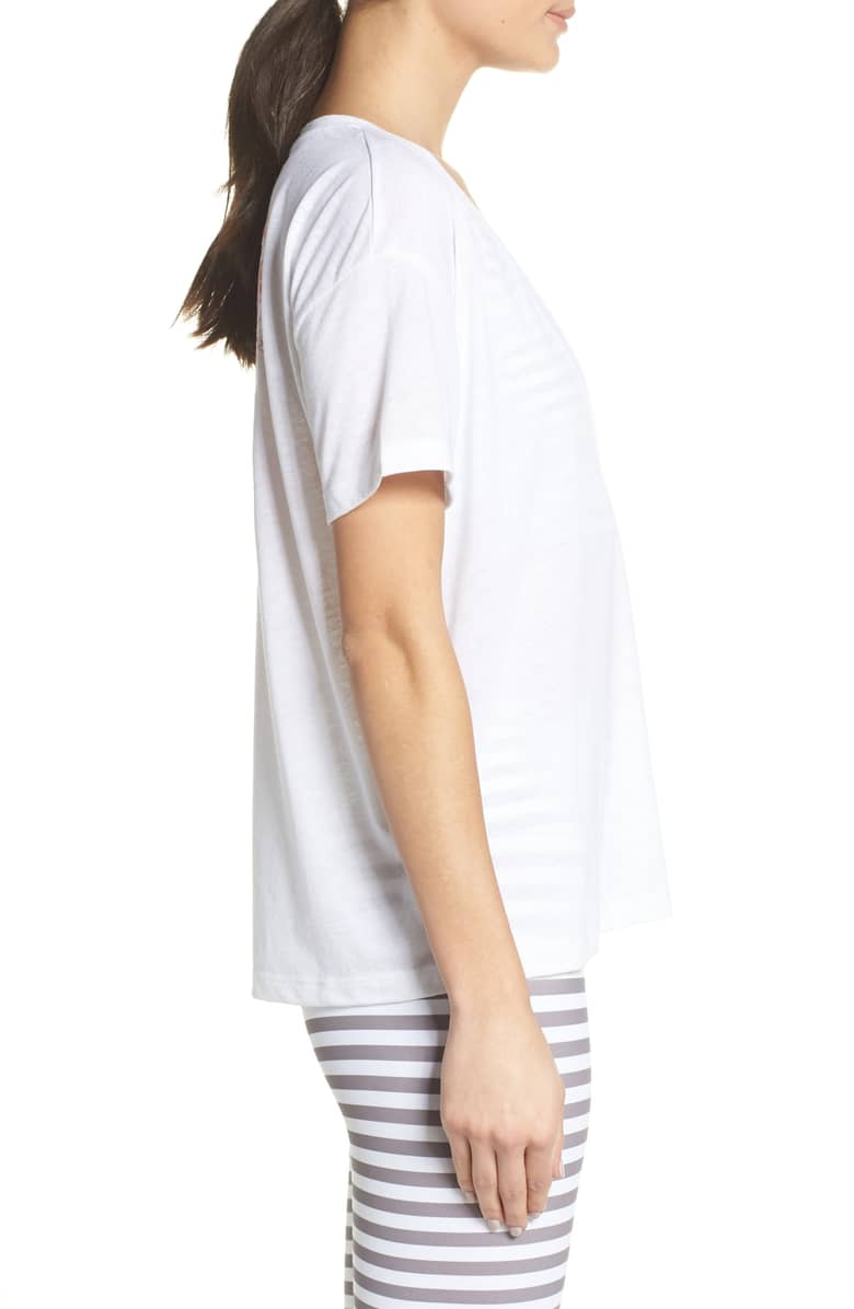 Side view of model wearing white n-neck t-shirt with an embroidered red heart on the left side.