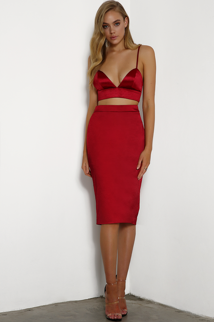 Jovana is wearing crimson red, satin, fitted, skirt that covers to just below the knee. The back features an exposed zipper and small split.