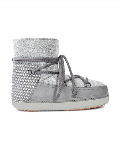 Pictured here is a winter boots with a light grey, rubber, waterproof, sole with a lace up and around the ankle tie in light grey. The boots are lining with light grey shearling and have a leather light grey instep. The ankle of the boots is embellished with a silver, metallic pattern.