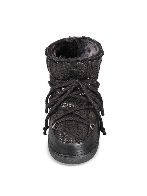 Pictured here is a dark grey winter boot with a dark grey, waterproof rubber sole that features a lace up and around the ankle tie. The instep is a dark grey, shiny knit and is lined with grey shearling.