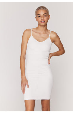 UNIKONCEPT Lifestyle boutique; image shows the Row Dress in white by Spiritual Gangster. This fitted mini dress features spaghetti straps and a plunging neckline. The fabric features a subtle ribbing detail that goes diagonal and vertical down the length of the dress.