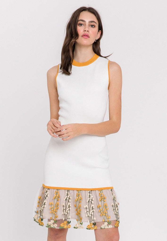 UNIKONCEPT Lifestyle boutique: the image shows the Gold Petals Mini Dress by Endless Rose. This dress is a fitted knit white dress with a golden trim along the neck line and sleeves. The dress features a mesh embroidered, floral, peplum style bottom. The back features a discrete but visible white, quarter zipper.