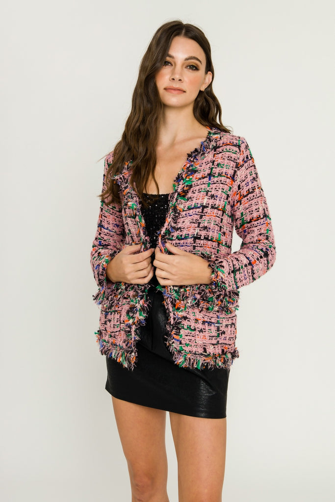 UNIKONCEPT LIFESTYLE BOUTIQUE: The model is wearing the Gabrielle Tweed Blazer by English Factory. This tweed blazer is pink with black, white, green, orange, blue and silver colours throughout. It has a fringe detail all around the front seam, two front pockets and one hook and eye closure.