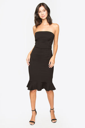 Model is wearing a black, strapless, body-con dress with a ruffle detail on the hem.