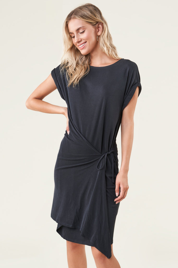 UNIKONCEPT Lifestyle boutique: the image shows the Forget Me Knot Dress by Sugar Lips. This knit midi wrap dress is black has a t-shirt dress silhouette with a tied waist sash detail and rolled sleeves. It features a crew neckline and sits just above the knee.