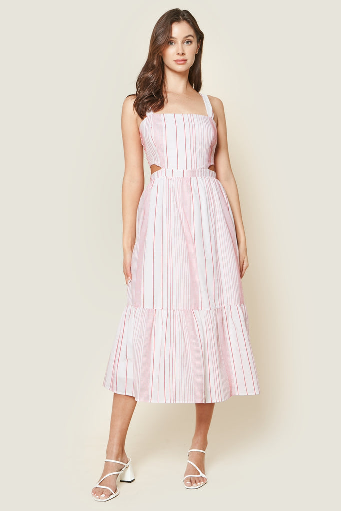 UNIKONCEPT Lifestyle boutique: This image shows the St. Tropez Striped Midi Dress by SugarLips. This midi dress is shaped with thick spaghetti straps, a fitted bodice with a cutout along the waistline on either side, a smocked back and a maxi skirt. The waist is made comfortable and accentuated with an elastic as it flows into a cascading, woven skirt. The fabric is made of muted red and white vertical stripes of different widths and distances apart.