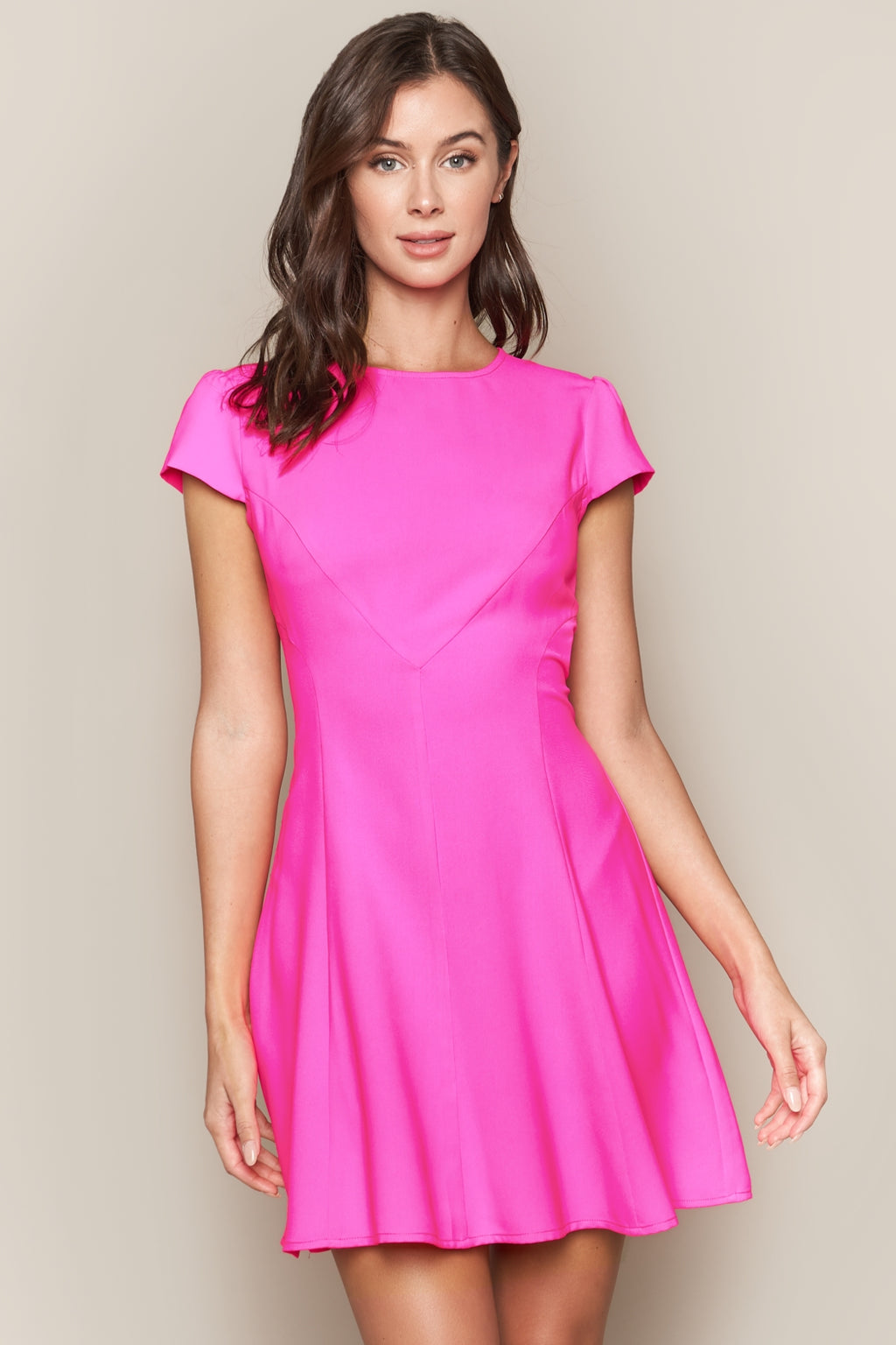 UNIKONCEPT: Lifestyle boutique; image shows a bright, hot pink a-line styled dress by sugar lips. The Bueno hot pink a-line dress features a short sleeve and tight bodice with asymmetrical stitching throughout. The dress is loose from the waistline to the bottom to showcase the a-line style.