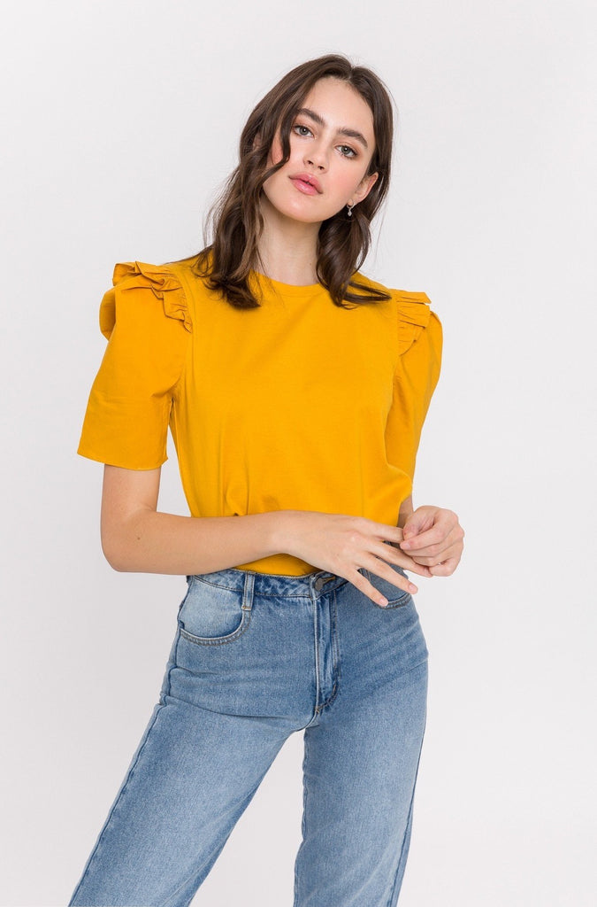 UNIKONCEPT Lifestyle boutique; image shows the Elevated Puff Sleeve Tee in mustard by English Factory. This relaxed tee features a crew neckline and puffed sleeves adorned by a ruffle detail on the shoulder of the shirt.