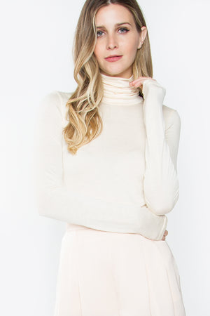 UNIKONCEPT Lifestyle boutique: Model wearing creme coloured, lightweight sugar lips turtleneck. The Molina Turtle Neck is a long sleeved cream turtle neck and is true to size, tight fit