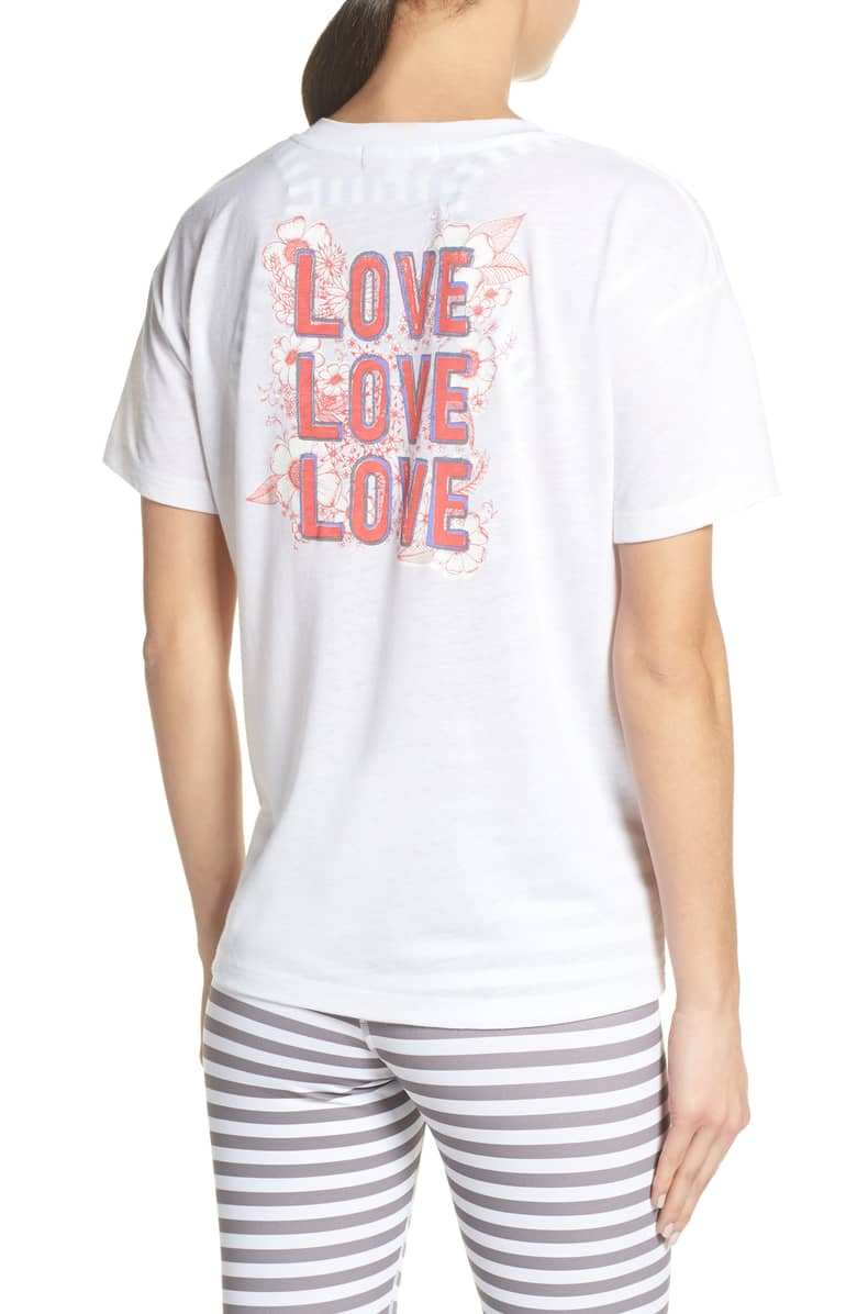"Back view of model wearing a white t-shirt with ""Love, Love, Love"" written in pink writing."