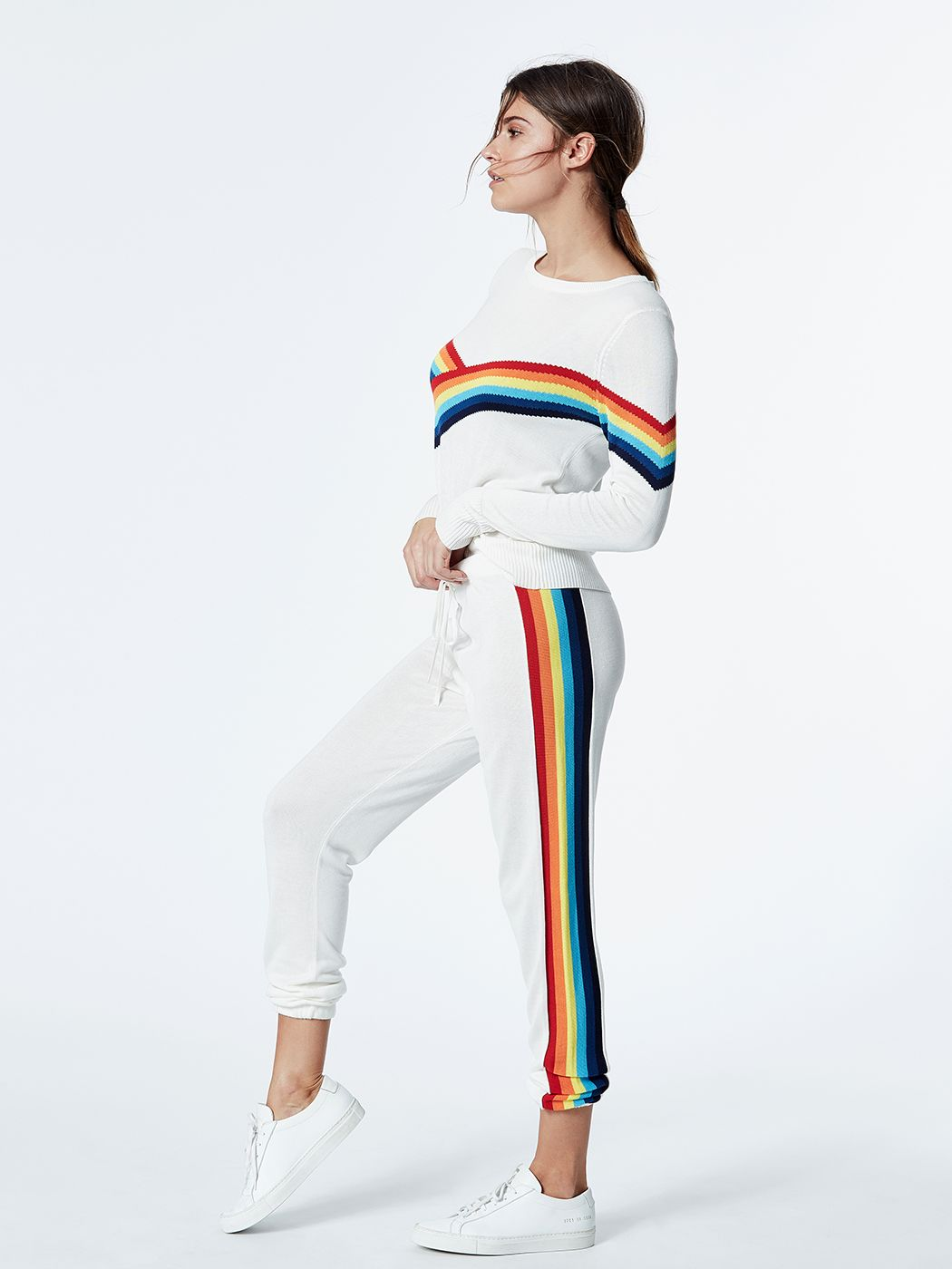 Model is wearing white, loose-fitting, tapered sweatpants with tie waist and elastic band bottoms. The pants feature a rainbow stripe running alongside the legs.