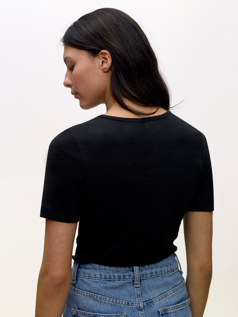 Model wearing black, crew neck, slim, KOTN t-shirt. View of Models back.