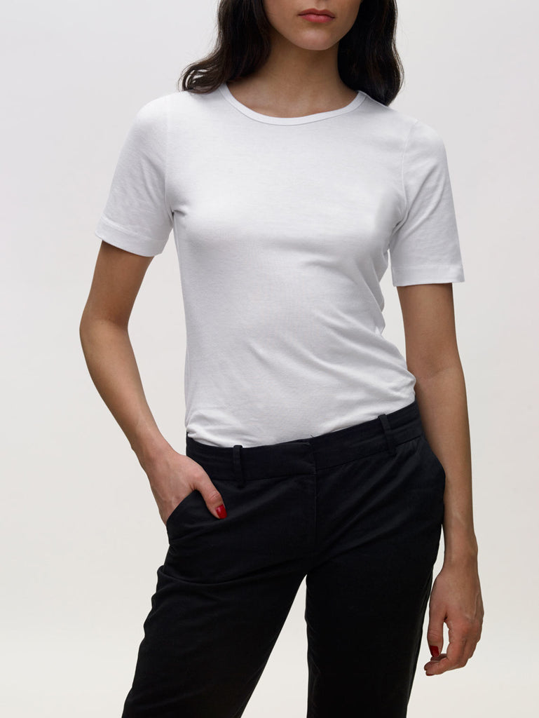 Model wearing white, crew neck, slim, KOTN t-shirt.