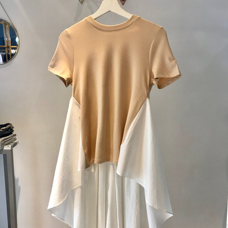 UNIKONCEPT: Lifestyle boutique; image shows a t shirt styled English factory top. The Darcy top is an almond base t shirt with a long white train. It starts at either side of the ribcage goes straight down to the hips and trails behind to about your ankle.