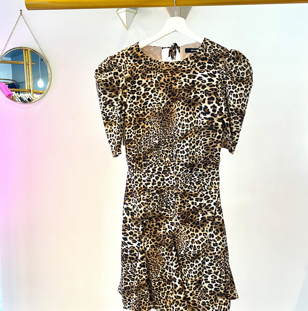 UNIKONCEPT: Lifestyle boutique; image shows a short sleeved ruffle leopard dress by sugar lips. The amuse me leopard print mini ruffle dress features a puffy short sleeve and tight waistband so the top billows and the the waist down is hugging and very flattering. It is an aline style with small ruffled pleats at the bottom.