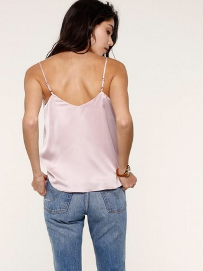 Model is wearing a Heartloom baby pink, satin camisole. The Andra cami comes with lace detail around the v-neckline and has spaghetti straps with a semi - open back.