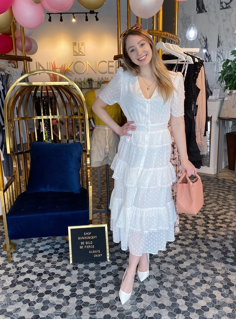UNIKONCEPT Lifestyle boutique: The image shows the Hamptons White Dress by Free the Roses. This white, ankle length button down dress is extremely elegant with a v-neck and relaxed billowing short sleeves. The fabric is made with small white dots on the white base to add some dimension. The long skirt is tiered and ruffled with a lattice lace detailing as a trim on each layer.