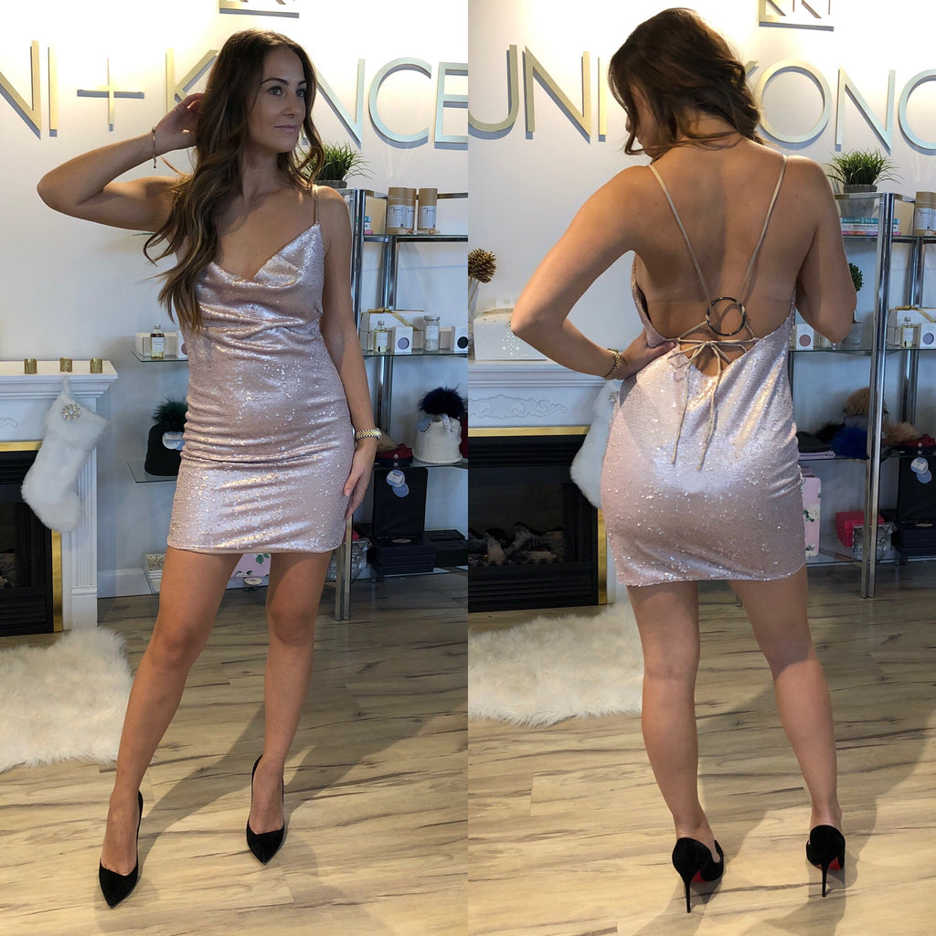 Model is wearing body con, pink sequin, cowl neck runaway mini dress. The Bijou sequin dress features a tie back closure around a ring detail with spaghetti straps.