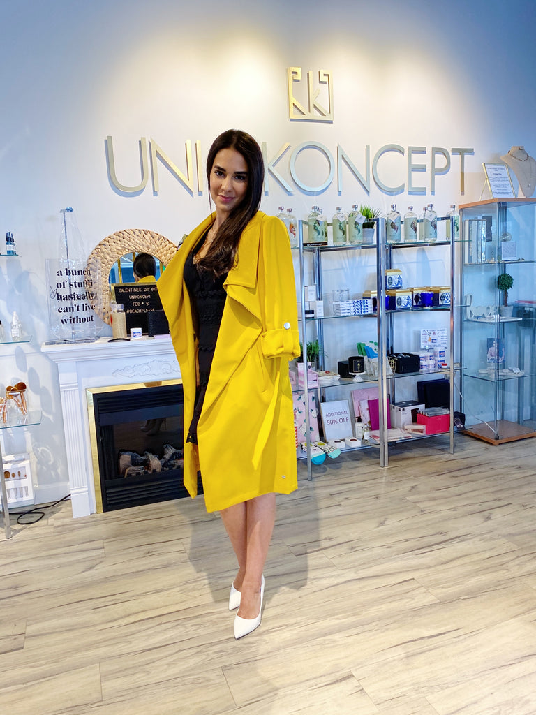 UNIKONCEPT: Lifestyle boutique; image shows a black trench coat by son and kyo. The Ornella coat in sunflower features pre rolled sleeves fashioned with silver buttons, a large collar and a stretchy belt matching the fabric and colour of the trench. It is mid length and can be worn multiple ways.