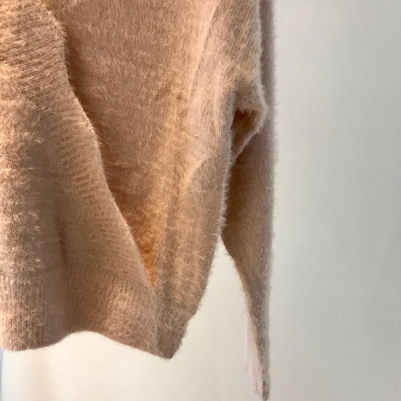 UNIKONCEPT: Lifestyle boutique; Image shows a pale pink v neck sweater by En creme. The Cotton Candy scallop edge sweater features a scalloped edge diagonally across the body. It is a basic crewneck style with an elastic waistband and elastic sleeves it also features a fluffy like texture from the knit used throughout.