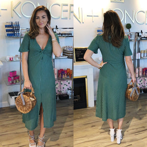 Model wears an emerald green mid length dress. The twist front midi dress has white horizontal stripes, a v neckline, short sleeves and a middle slit.