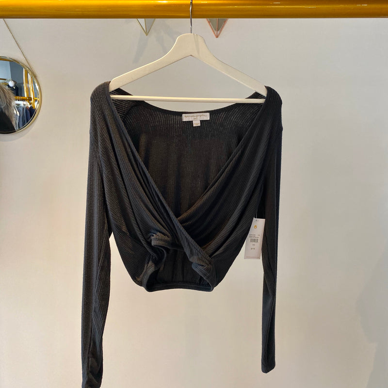 UNIKONCEPT: Lifestyle boutique; Image shows a long sleeve vintage black ribbed cropped top. The ballet ribbed surplice top features an elastic waistband and a faux wrap top.