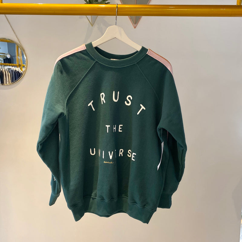 "UNIKONCEPT: Lifestyle boutique; Image shows a classic crewneck by Spiritual Gnagster. The classic crew sweatshirt in the colour jade features linear sleeve detailing with shades of glittery pink stripes and white writing at the front stating, ""trust the universe"""