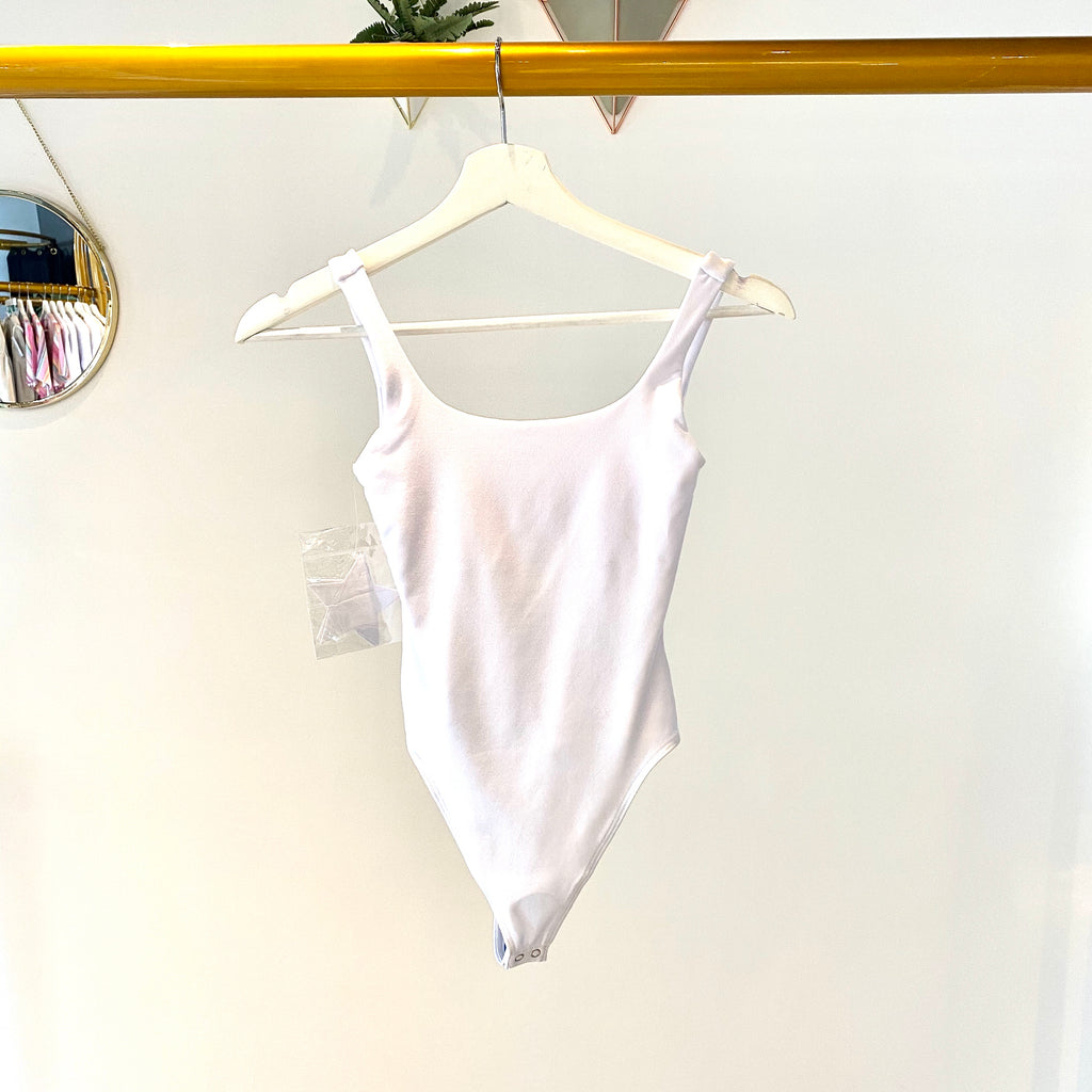 UNIKONCEPT Lifestyle boutique: this image shows the White Tank Bodysuit by Good American. This ultra-soft matte white bodysuit is a tank top with a low cut front and back squared neckline. The bodysuit is a clasped thong cut allowing for over head dressing.
