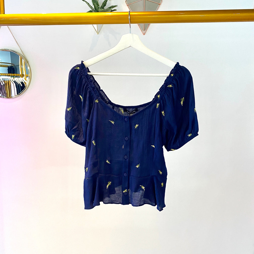 UNIKONCEPT: Lifestyle boutique; image shows a navy blue short sleeve peplum blouse by sugar lips. The Chasing highs embroidered peplum top features small embroidered florets throughout the top and button closures in the centre of the blouse. Can be worn on or off the shoulder.