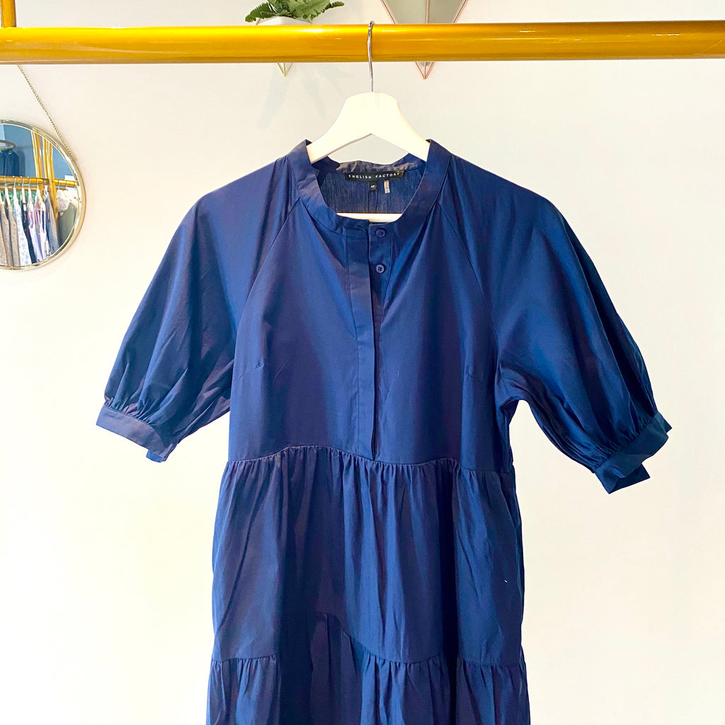 UNIKONCEPT Lifestyle boutique; image shows the Cecile dress in navy blue by English Factory. This dress features a three tiered a-line skirt, billowed and cuffed sleeves as well as button closures down the chest.