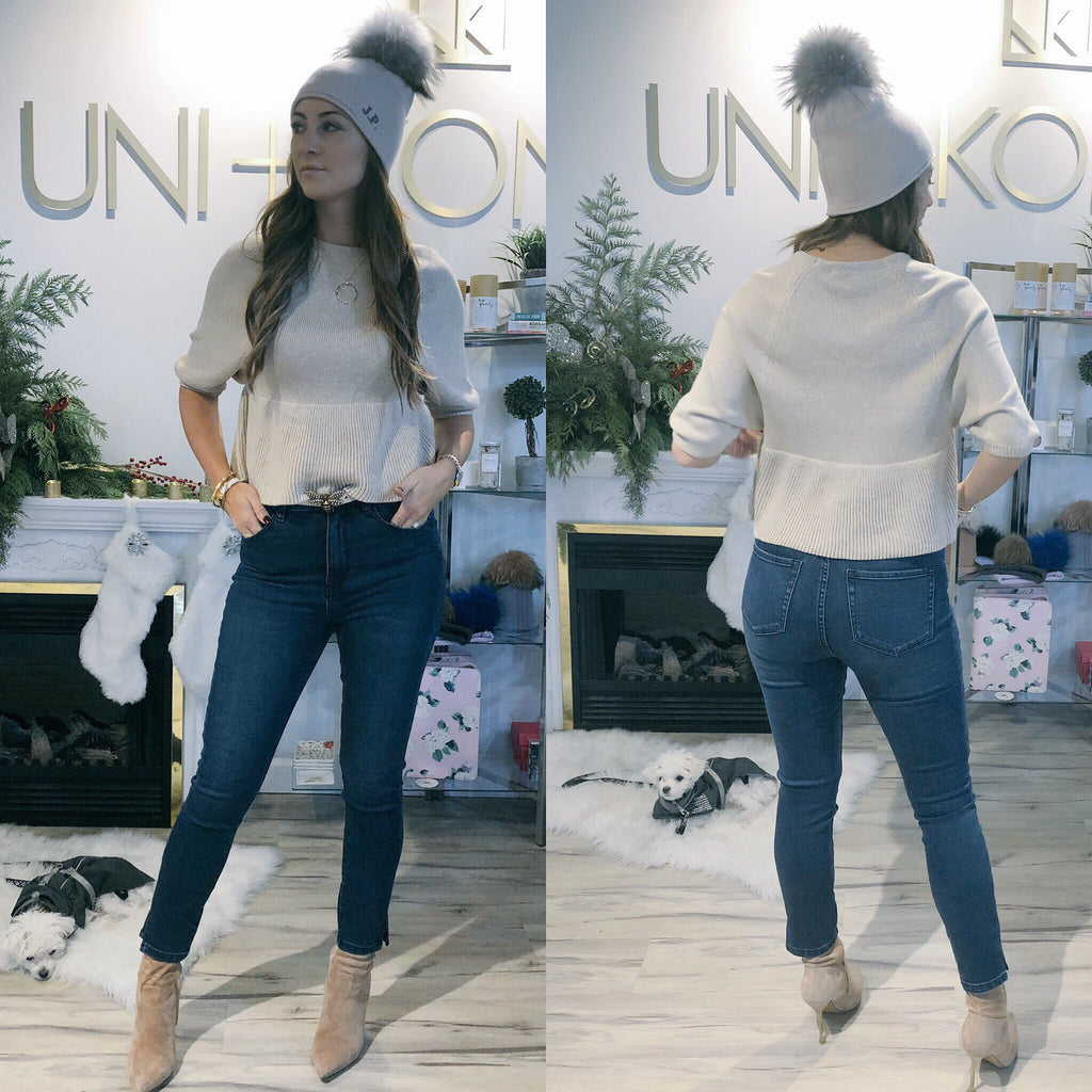 Model is the Bella split blue jean by Neon Blonde. This jean is mid wash, high rise and skinny cut. Ankle length jeans, with split hem. Front view on left, and back view on right.