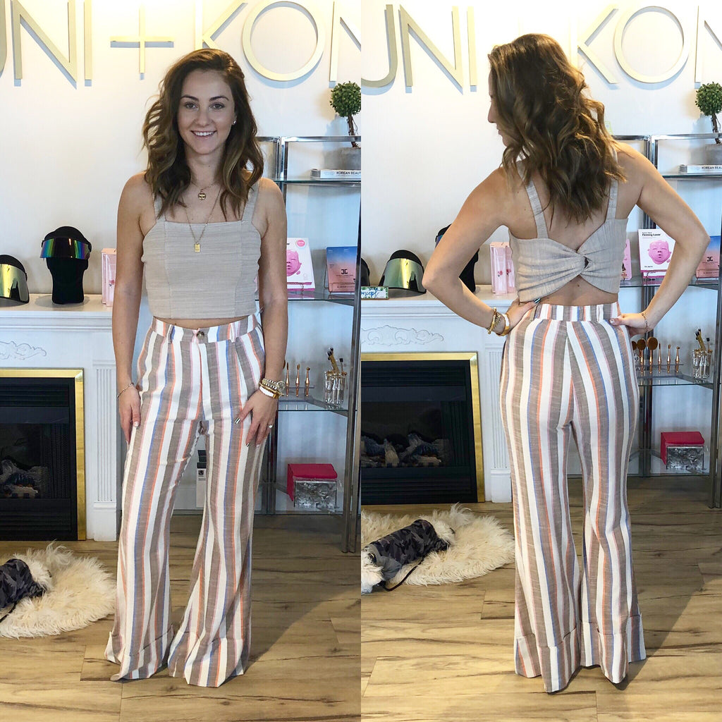 UNIKONCEPT Lifestyle boutique: Model is wearing white, tan, dusty red and baby blue vertical stripped, show me your mumu pants. The Edison stripe pants feature a gold button and a high waist.