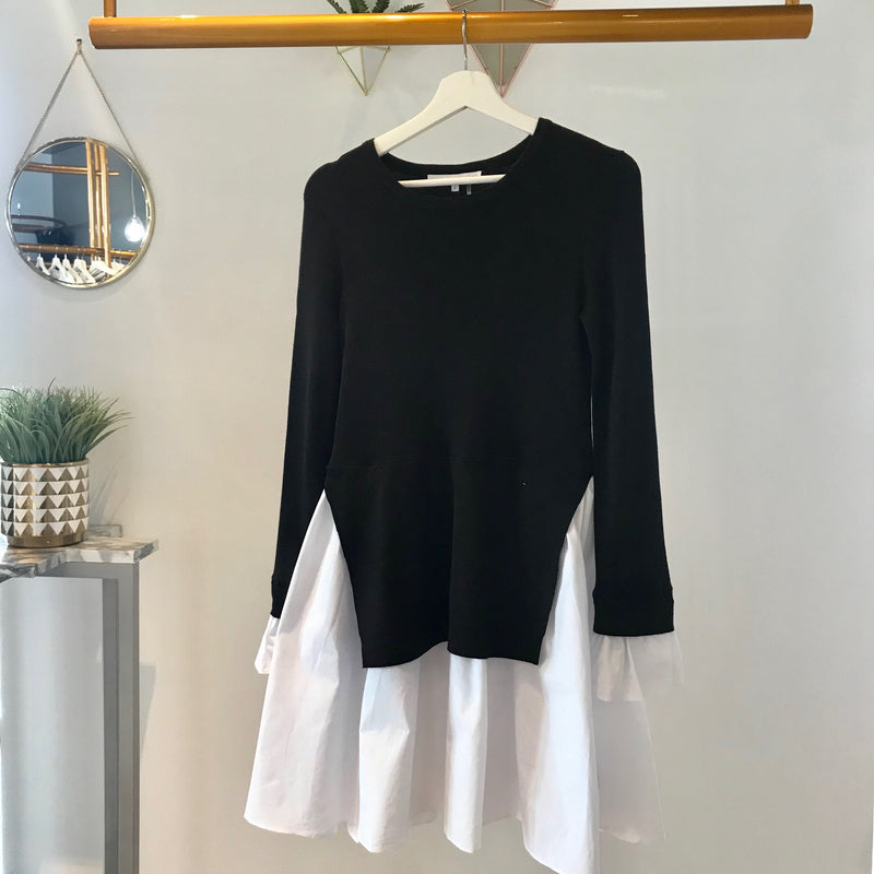 UNIKONCEPT Lifestyle boutique: Image shows a two tiered English factory dress. The Sofia dress in black is a long sleeve dress with two layers. Underneath is a white a-line skirt with an black knit overlay. The Sofia dress also features the same white material on the sleeve to create a bell like sleeve.