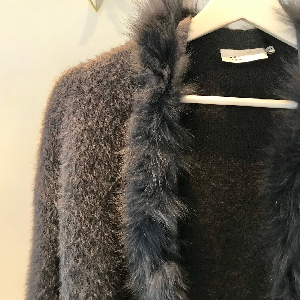 UNIKONCEPT: Lifestyle boutique; Image shows a dark grey cardigan by The room. The Pricilla cardigan features a faux fur trim around the neckline all the way down to the end of the cardigan. It also features square pockets on either side.