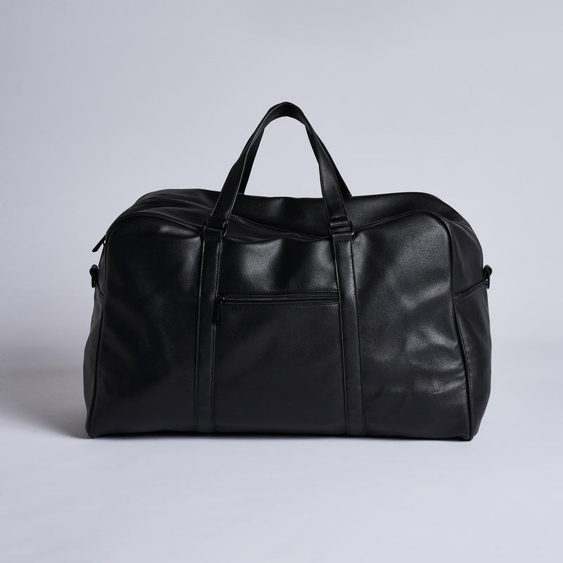 Image shows a large, black weekend duffle bag by pixie mood. the Frances weekender bag has a large, green envelope  like compartment on the front of it as well. The bag has large handles at the top.