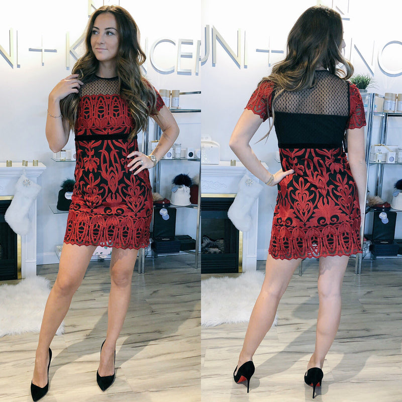 Model is wearing red lace, fitted, cap sleeve Foxiedox dress with black lining. The Rosa Lynn Dress has a neckline with sheer black trim, with a black band around the waist. At the back is a large black band around waist and sheer black trim at the top.