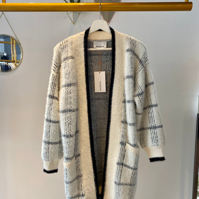 UNIKONCEPT: Lifestyle boutique; Image shows a white, super soft heart loom cardigan. The sheri cardigan features puffy sleeves, a white base with black and grey plaid like print and two side pockets. It also has black detailing around each hemline and a grey fleece interior.