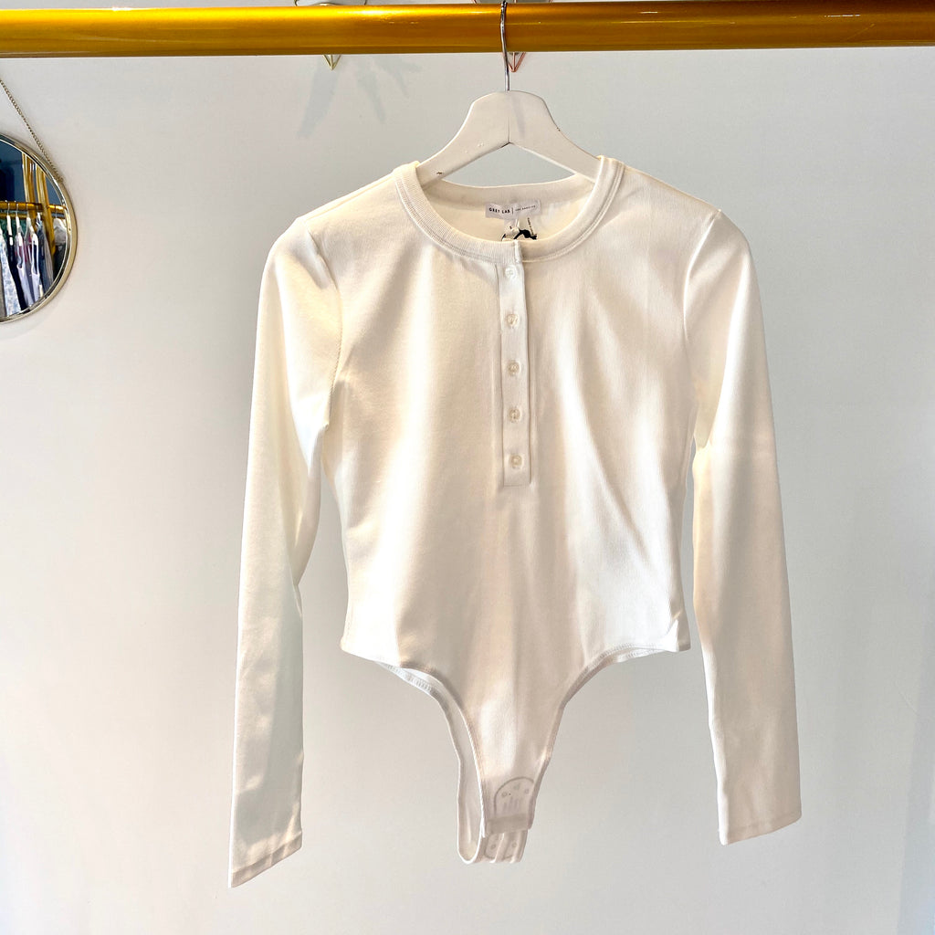 UNIKONCEPT Lifestyle boutique: image shows the Trina Long Sleeve bodysuit in white by Grey Lab. This fitted long sleeve bodysuit features a crew neck and button closures that go three quarters of the way down the front. There are also button clasps at the bottom of the bodysuit making it easy to put on and take off.
