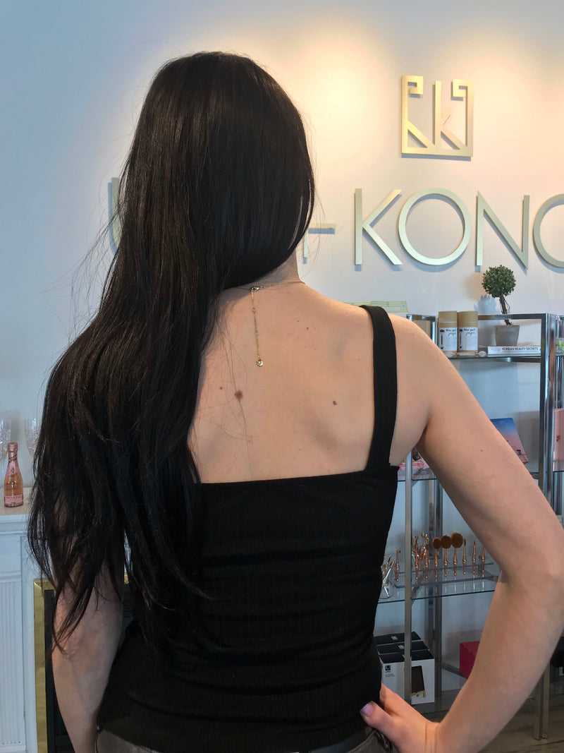Model wearing black tank top with ribbed details, thick straps, and front cutout. View from back