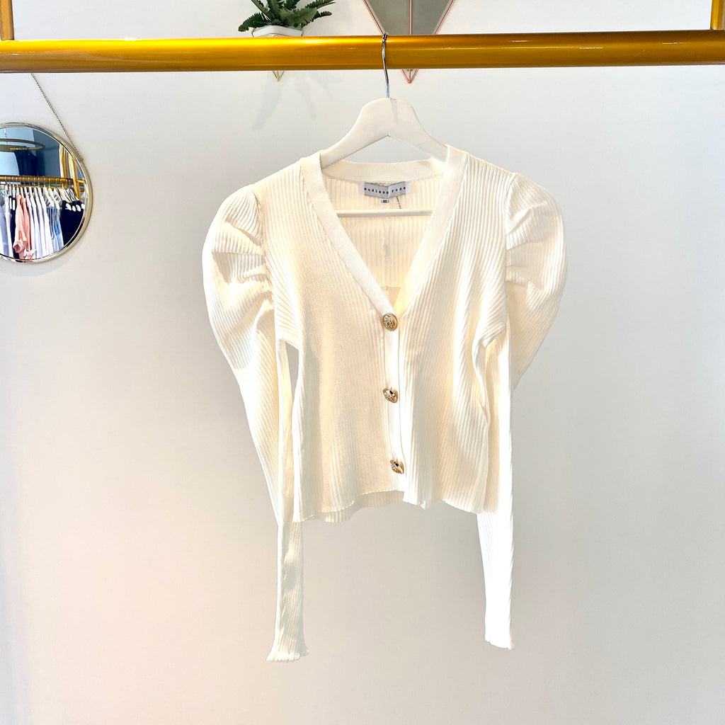 UNIKONCEPT Lifestyle boutique: the image shows the Sharp Shoulders Cardigan by Endless Rose. This long-sleeve, fitted, pant length cardigan is white and features three golden accent buttons down the front which also act as a closure. The shoulders feature a pleated puff detail that extends down the arm slightly.