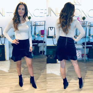 Jovana is wearing navy, velvet mini skirt with ruffle hem that wraps towards the top left of the skirt.