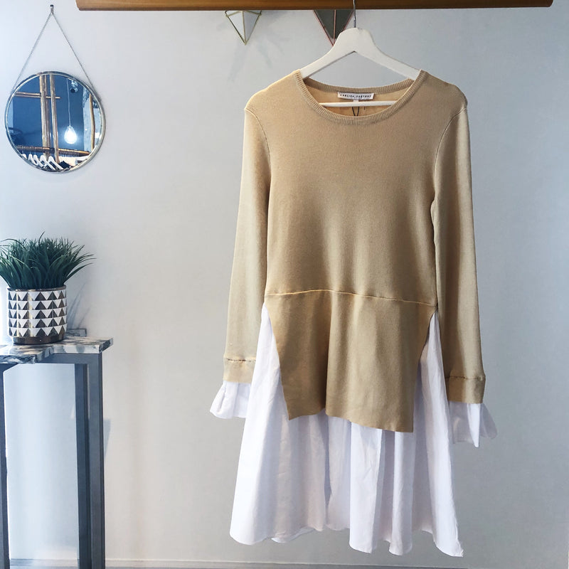 UNIKONCEPT Lifestyle boutique: Image shows a two tiered English factory dress. The Sofia dress in almond is a long sleeve dress with two layers. Underneath is a white a-line skirt with an almond knit overlay. The Sofia dress also features the same white material on the sleeve to create a bell like sleeve.