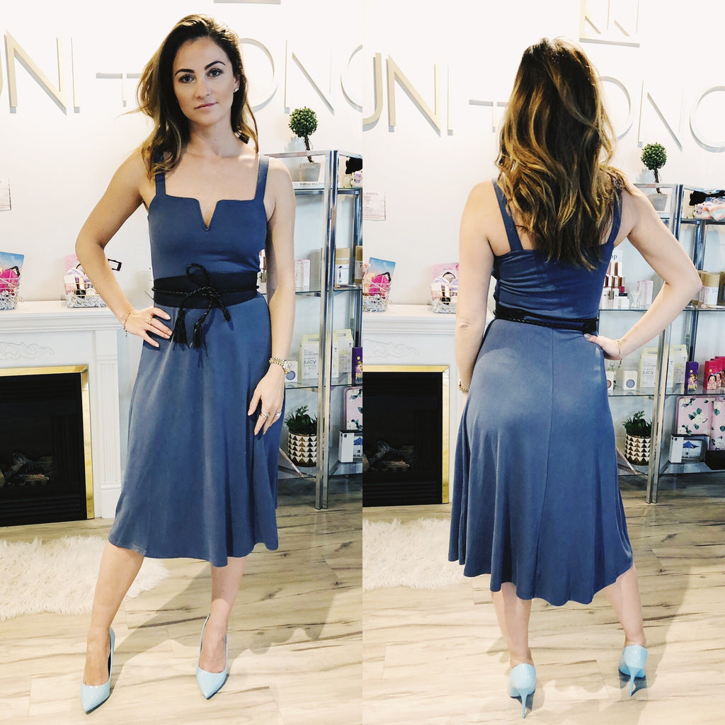 Model wears a muted blue Heartloom midi dress. The Dallas dress has thick spaghetti straps, a square neckline and a small V shaped diet in the centre of the neckline for a flattering shape. The Dallas dress is A-line.